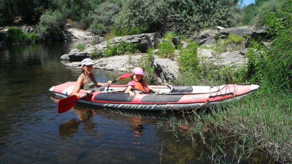 Moeder met kind in een stabiele kayak op onze rivier.activiteiten